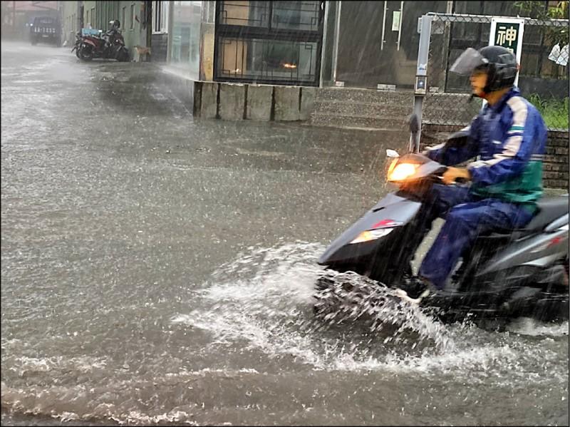 曾被視為高市府清淤指標之一的鳥松區神農路,昨積水約半個輪胎深,騎士水中行車備感不便。(中央社)