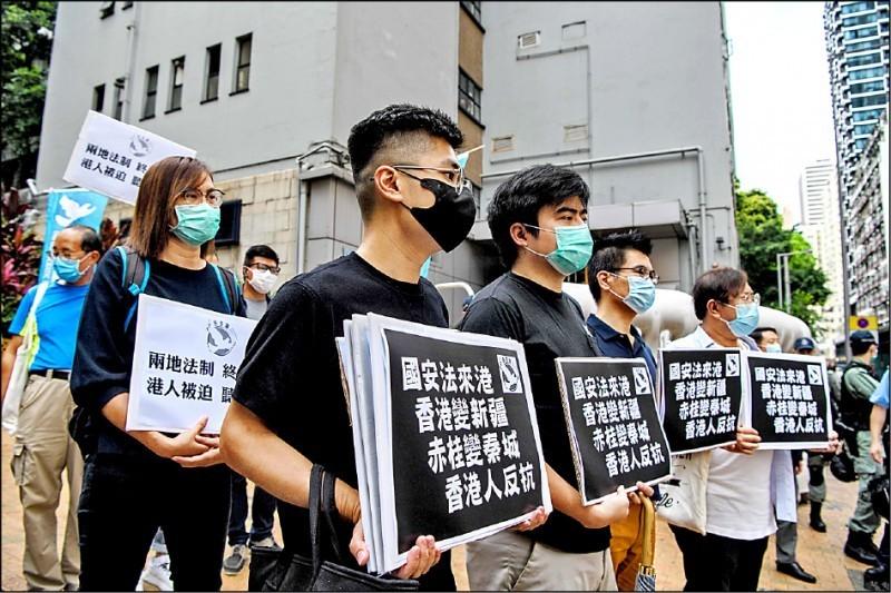 香港民主黨人士22日持標語遊街抗議中國人大擬制定港版國安法。(法新社)