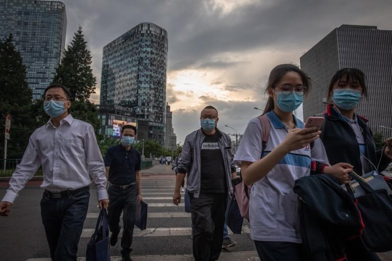 中國北京民眾戴口罩上街。(歐新社)