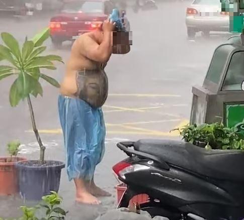 男子用雨水大力搓洗頭部,接著還撿起一頂藍色塑膠帽戴上,奇怪舉動引發網友熱烈討論。(圖擷取自臉書)