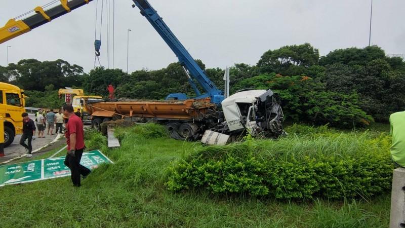 砂石車衝進竹南交流道分隔島,大面指示牌遭撞斷,砂石車頭全毀,駕駛輕傷送醫。(記者鄭名翔翻攝)