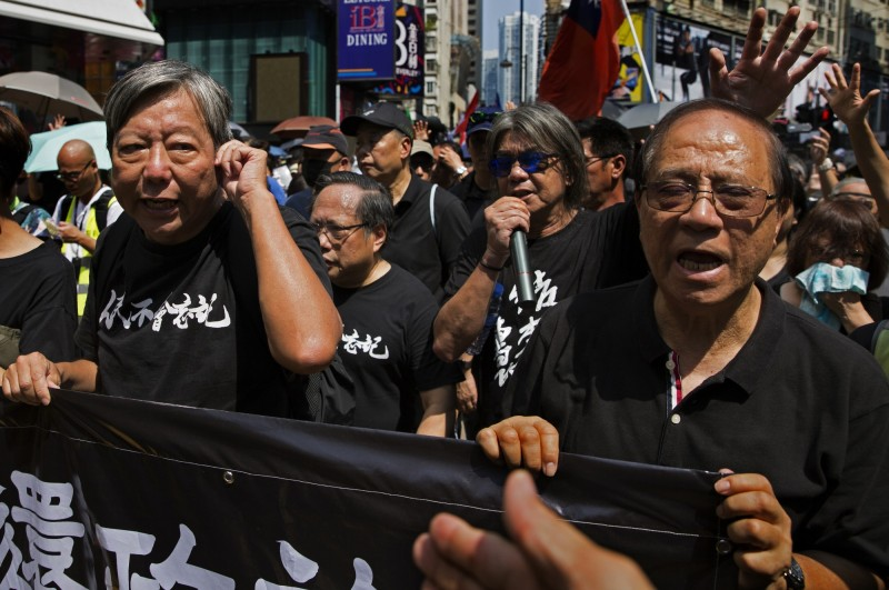 圖為2019年10月1日,前香港立法會議員「長毛」梁國雄(右2)等泛民主派人士,走上街頭反對香港政府和北京。(美聯社檔案照)
