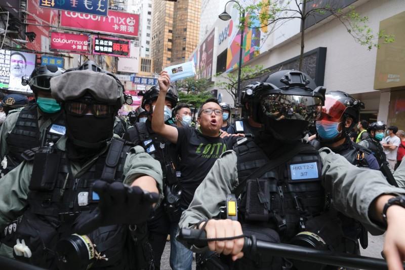 香港民眾群起反對港版國安法的修訂,今(24日)紛紛走上街頭抗議,但民主派政黨「人民力量」的副主席譚得志(中)卻被警方當街逮捕。(法新社)