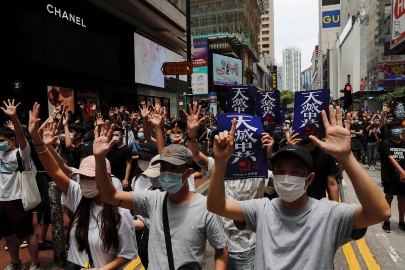 香港銅鑼灣現場人滿為患,許多民眾手持「天滅中共」標語。(路透)