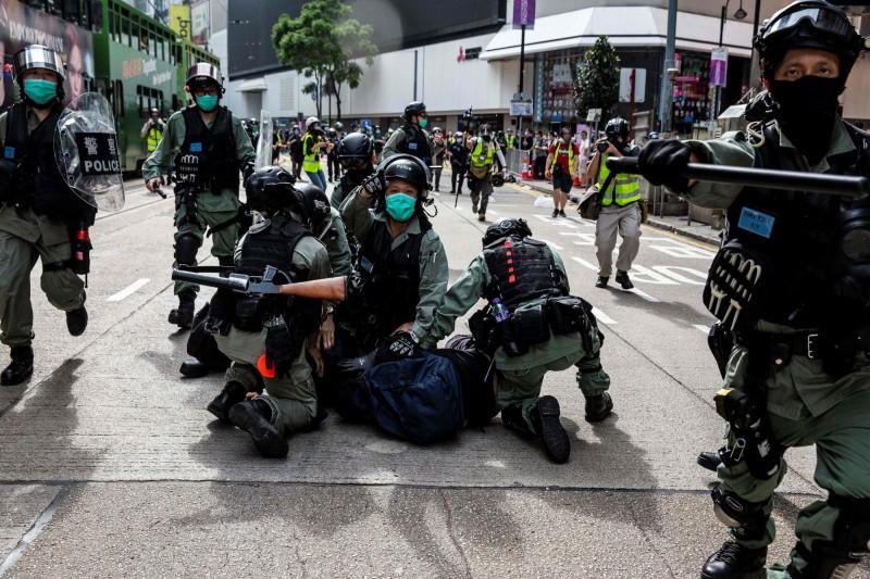 香港民眾今再度上街反對「港版國安法」和「國旗法」立法。國民黨強調,國民黨始終支持香港地區保持有別於大陸地區的民主與自由,早日落實「雙普選」,港府與中共當局應盡速建立與反對群眾的溝通管道,以利維持香港的安定。圖為香港警方今天下午在銅鑼灣街頭壓制、逮捕抗議中國推動港版國安法的示威者。(法新社)