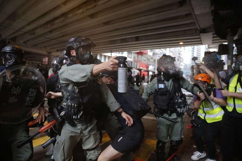 香港警方在制服民眾期間,朝記者聚集位置使用胡椒噴霧。(美聯社)