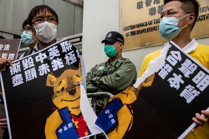 香港反對國安法人士走上街頭,撕毀「小熊維尼看板」。(法新社)