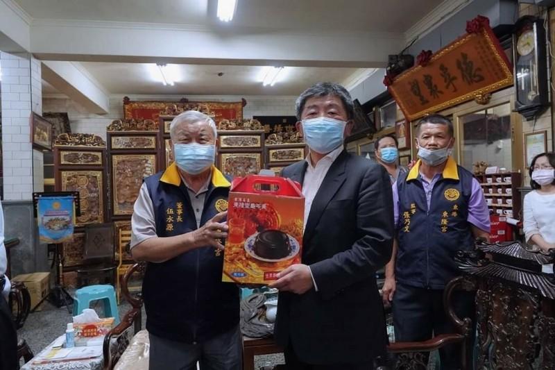 陳時中(左2)接下東隆宮董事長伍水源轉贈的「龜苓膏」,今天居家隔離也「歸零」。(記者陳彥廷翻攝)
