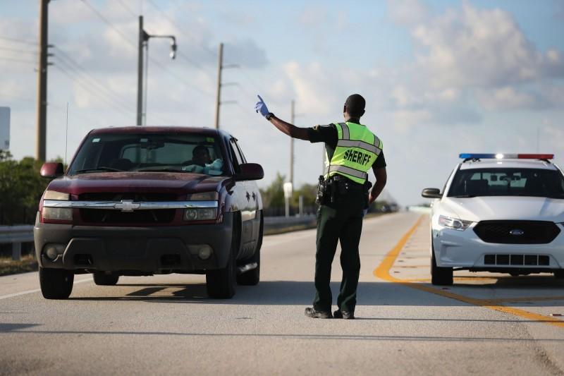 美國佛州礁島群設置武漢肺炎(新型冠狀病毒病,COVID-19)檢查站,只有當地居民才能進入,1名男子為了順利通過哨站竟挾持居民開車。佛州礁島群檢查站執法人員示意圖。(法新社)