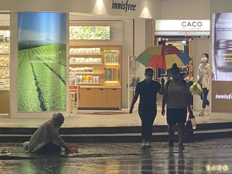 街友在大雨中乞討。(記者黃旭磊攝)