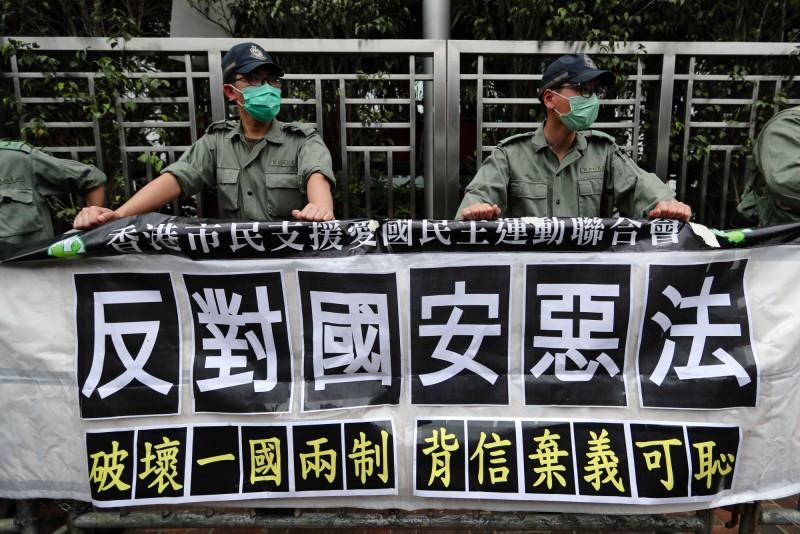 「香港抗爭者支援工作台灣義務律師團」發言人林俊宏提醒,「港版國安法」28日通過,加上疫情趨緩邊境解封,未來預期將會有另一波港人來台申請政治庇護,政府須做好準備。圖為香港市民在中聯辦外掛「反對國安惡法」抗議布條。(彭博)