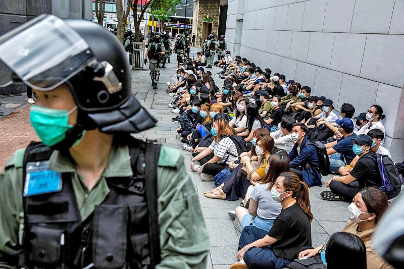 Police officers detain a group of protesters in the Causeway Bay area of Hong Kong yesterday.  Photo: AFP