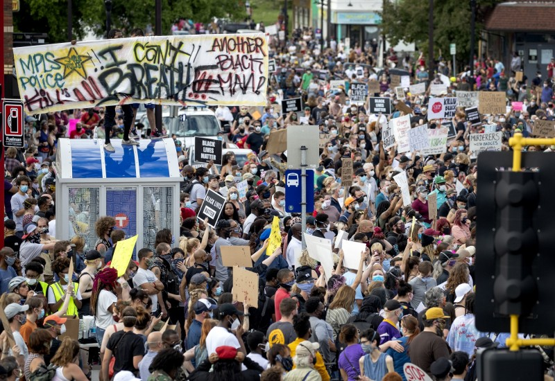 數百民眾重返現場,高舉字牌為死者討公道。(美聯社)
