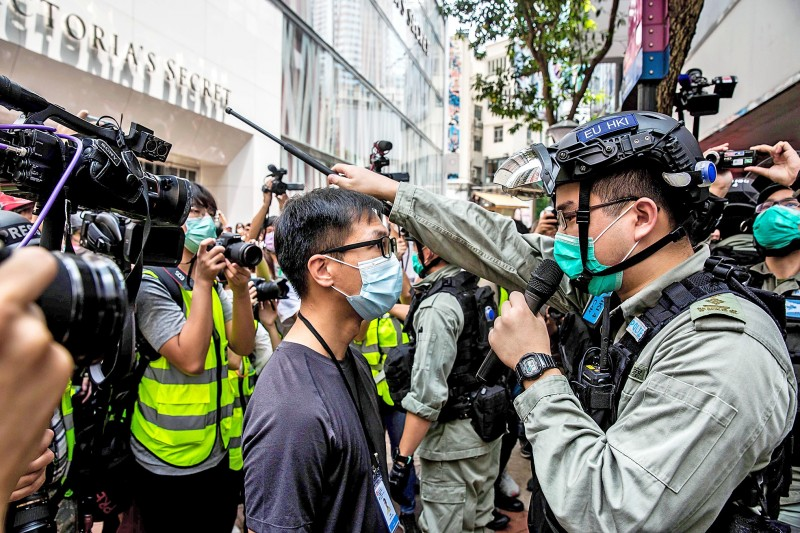 A police officer, right, guards the entrance to an MTR station near the Legislative Council in Hong Kong yesterday.  Photo: AFP
