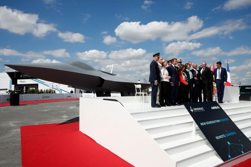 德國、法國和西班牙聯合開發第6代戰鬥機,名為「未來空中戰鬥系統」(FCAS)計劃。圖為2019年巴黎航太展,法國總統馬克宏與眾人在FCAS模型前合照。(法新社)