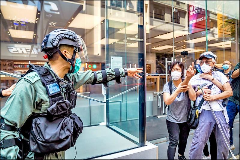 鎮暴警察在銅鑼灣逮捕示威者時,家長、銀髮族自發組成的「守護孩子」團體義工與警方發生口角。(彭博)