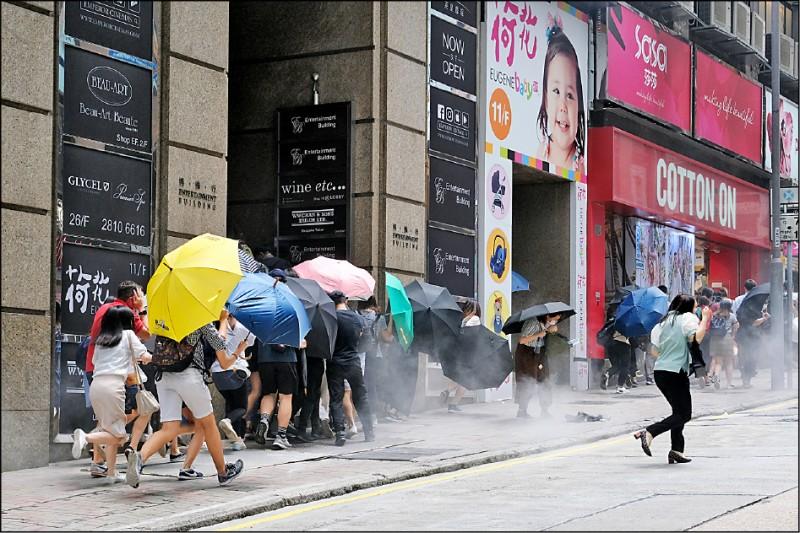 反國歌法、國安法的示威者與路人,在港島中環以雨傘遮擋鎮暴警察發射的胡椒彈。(彭博)