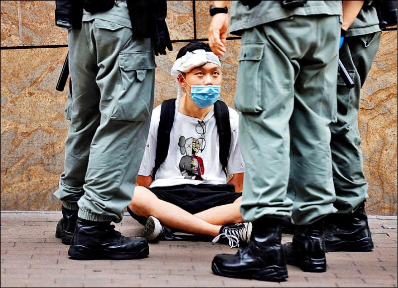 一名被捕的抗議人士二十七日在香港銅鑼灣被三名鎮暴警察包圍。(美聯社)