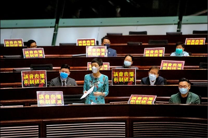 香港立法會二十七日起二讀辯論國歌條例草案,民主派會議召集人陳淑莊(中)及其他民主派議員,在座位上擺出標語,抗議惡法。(彭博)