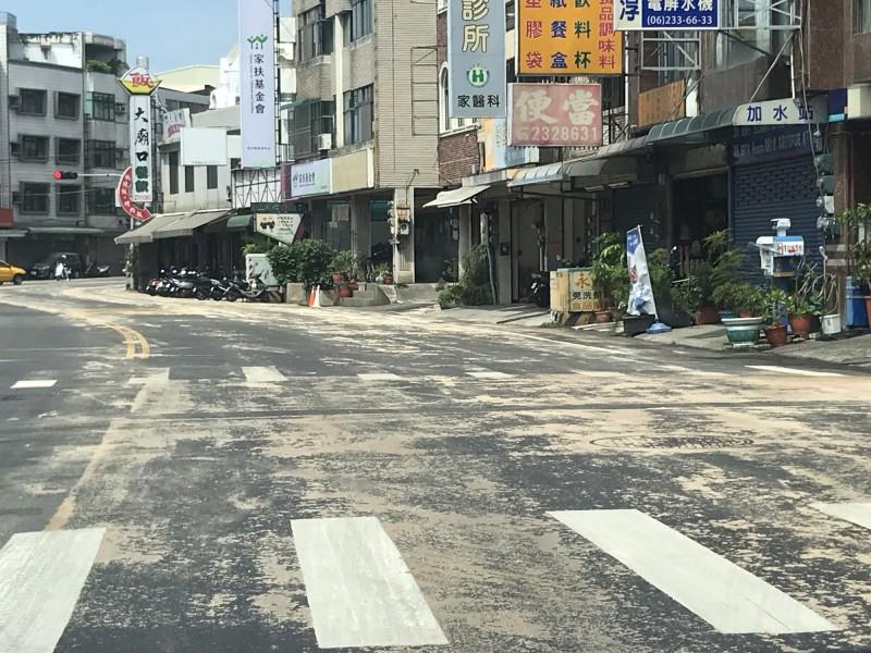 清理的木屑經車輛不斷壓過,造成永康中山北路多處路面髒亂,也引起用路人討論。(記者萬于甄攝)