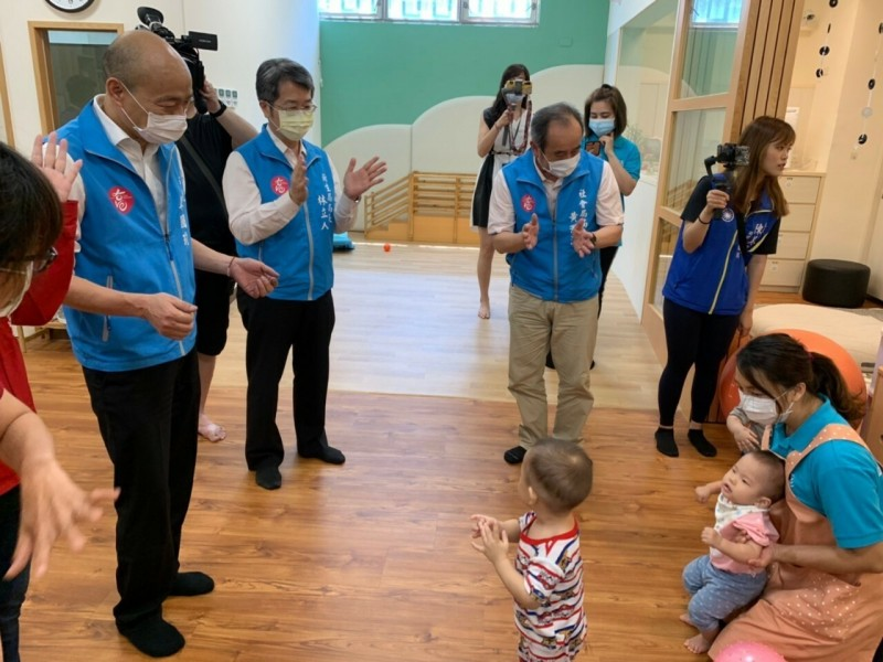 高雄市長韓國瑜(左起)、衛生局長林立人及社會局長黃淵源與托育寶寶互動。(記者黃旭磊翻攝)