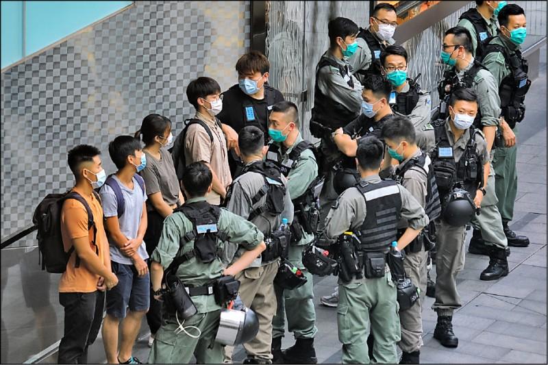 香港立法會27日起展開國歌法二讀辯論,港人從清晨起就在港島金鐘、中環、九龍旺角和新界等地示威,警方出動速龍小隊、鎮暴警隊等3000多名警力,在各處盤查民眾身分,包括身穿校服的學生,至晚間已逮捕逾300人,年紀最小者僅14歲。(彭博)