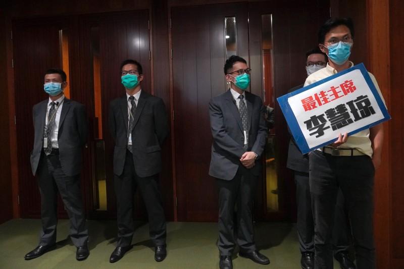 立法會議員朱凱迪(右一)展示「最佳主席李慧琼」標語,卻被指稱標語具侮辱性而遭抬離會議廳。(美聯社)