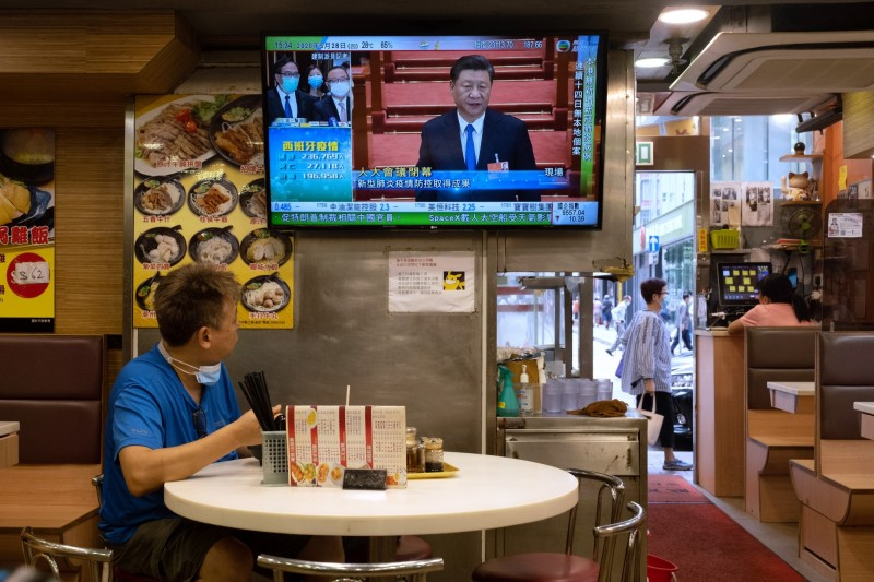 中國人大今天閉幕前通過港版國安法,圖為香港一家餐廳內消費者看著電視轉播。(彭博)