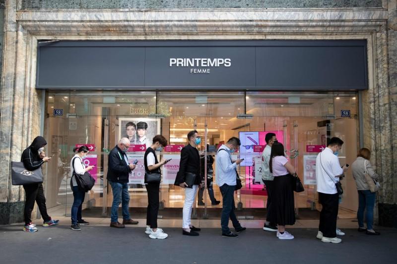 根據最新統計,武漢肺炎肆虐全球已奪走至少35萬5736條人命。圖為巴黎街頭人們戴著口罩準備進入百貨公司購物的畫面。(法新社)