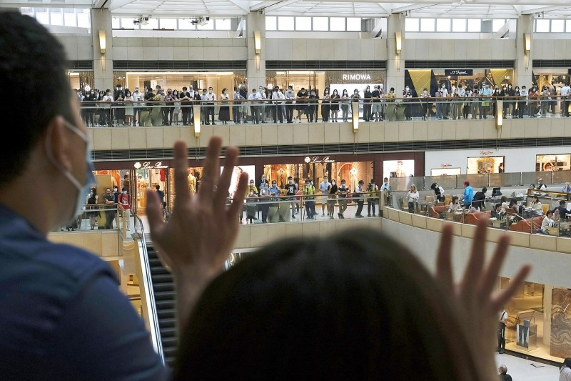 """People hold up fingers in a gesture endorsing """"five demands, not one less"""" at the Landmark shopping mall in Hong Kong yesterday. Photo: Bloomberg"""