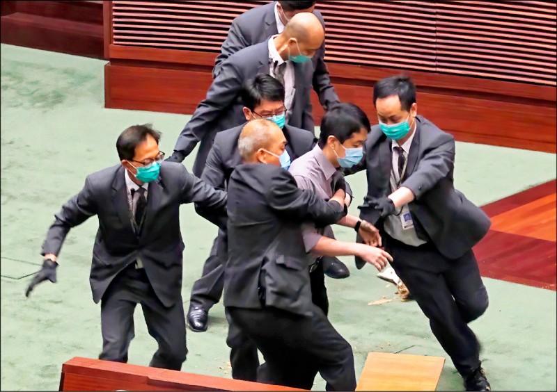 許智峯帶入立法會議場的腐臭盆栽被清除後,消防員穿戴防毒面具至議場內仔細檢查。(美聯社)