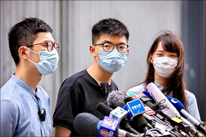 香港本土派政黨「香港眾志」重要成員羅冠聰(由左至右)、黃之鋒和周庭,廿八日在立法會外向媒體發表對美國認定香港不再享有自治地位的看法。(歐新社)