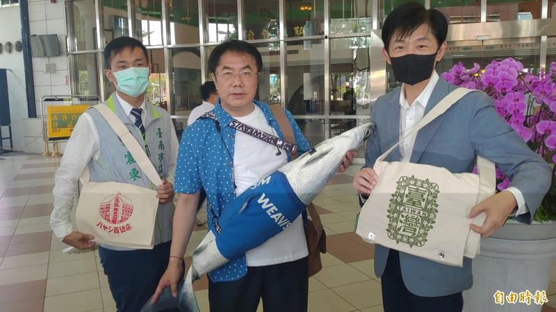 台南市長黃偉哲(中)展示為「防疫五月天」所準備的穿著服飾及虱目魚包,除了輕鬆休閒風外,也有滿滿的台南味。(記者蔡文居攝)