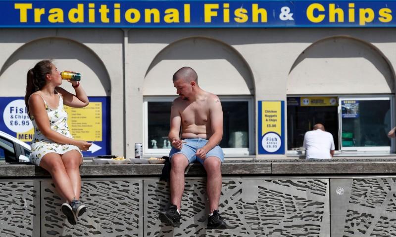 英國29日高溫創紀錄。圖為英國民眾炸魚薯條店前的堤防上喝啤酒、吃外帶炸魚薯條。(法新社)