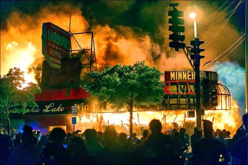 明尼亞波里斯第三分局旁的賣酒店也陷入火海。(法新社)