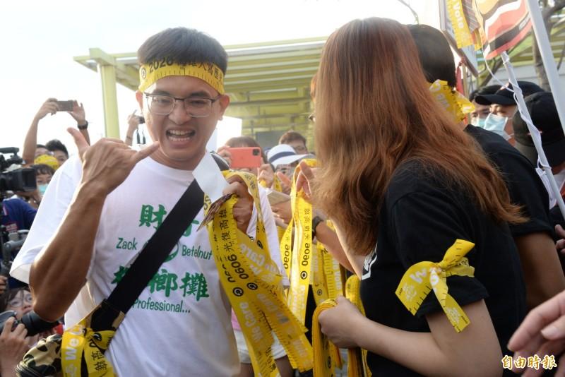 民眾拿到黃絲帶,興奮比6。(記者許麗娟攝)