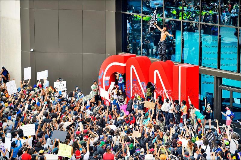 抗議人士29日集結於喬治亞州亞特蘭大的美國有線電視新聞網總部外,在巨大的CNN標誌上塗鴉。(美聯社)