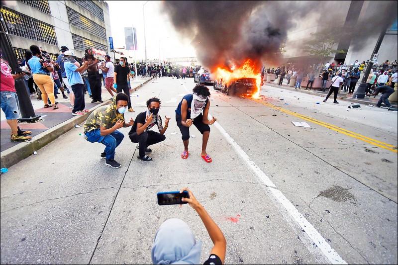 民眾在燃燒的警車前拍照留念。 (美聯社)