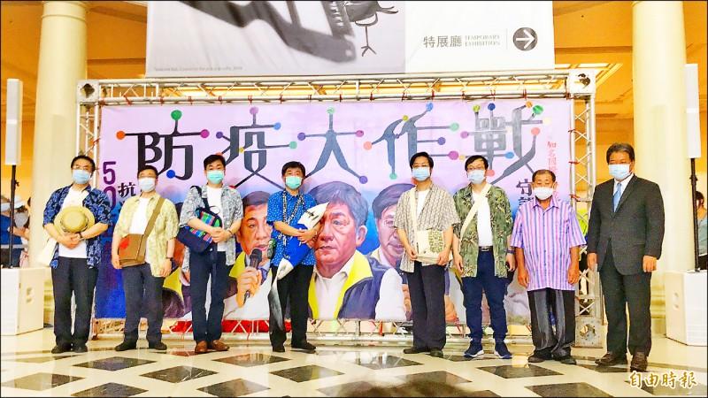 國寶級手繪電影海報看板大師顏振發手繪的「防疫大作戰」看板,昨在奇美博物館亮相,「防疫五月天」與台南市長黃偉哲也一冋在巨幅繪像前合影。(記者萬于甄攝)