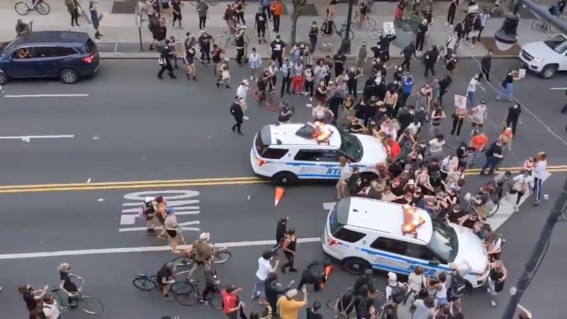 紐約市警局的2輛警車衝撞示威人群,導致多人向後重摔倒地。(擷取自Twitter@pgarapon)