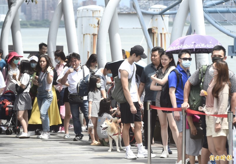 疫情趨緩加上天氣晴朗,台北淡水老街等景點人潮漸漸回溫,民眾在渡船頭排隊搭船。(記者簡榮豐攝)