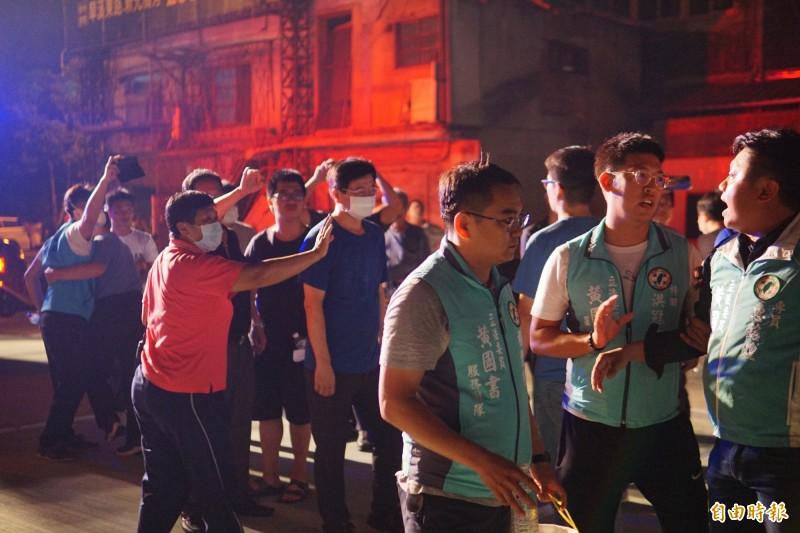 國民黨市議員羅廷瑋(左持手機者)和立委黃國書的專員惠銘煌(右一),在新民街火場爆發衝突。(記者何宗翰攝)