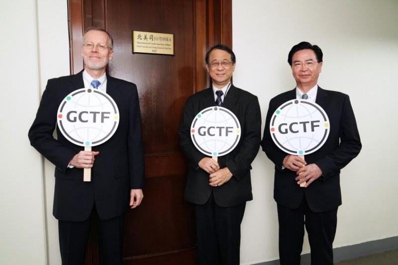 外交部長吳釗燮(右)與AIT處長酈英傑(左)及日本駐台代表泉裕泰(中)持「全球合作暨訓練架構」(GCTF)手牌,為GCTF秘書處揭牌合影。(外交部提供)