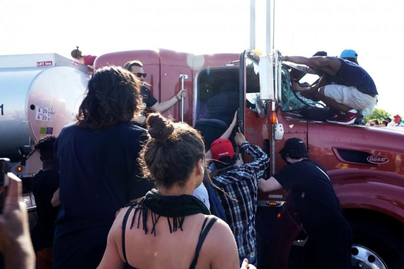 油罐車司機被憤怒的群眾拖下車圍毆。(路透)