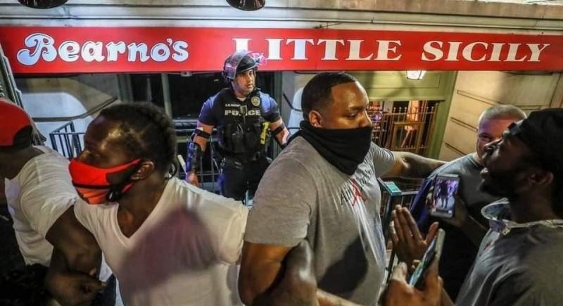 上月28日晚上一場在肯塔基州路易斯維爾舉行的抗議活動,有一名白人警察在街頭落單,被示威民眾逼到角落,沒想到這時有多名黑人民眾站了出來,手牽手拉起人龍保護這名落單的員警。(圖擷取自推特)