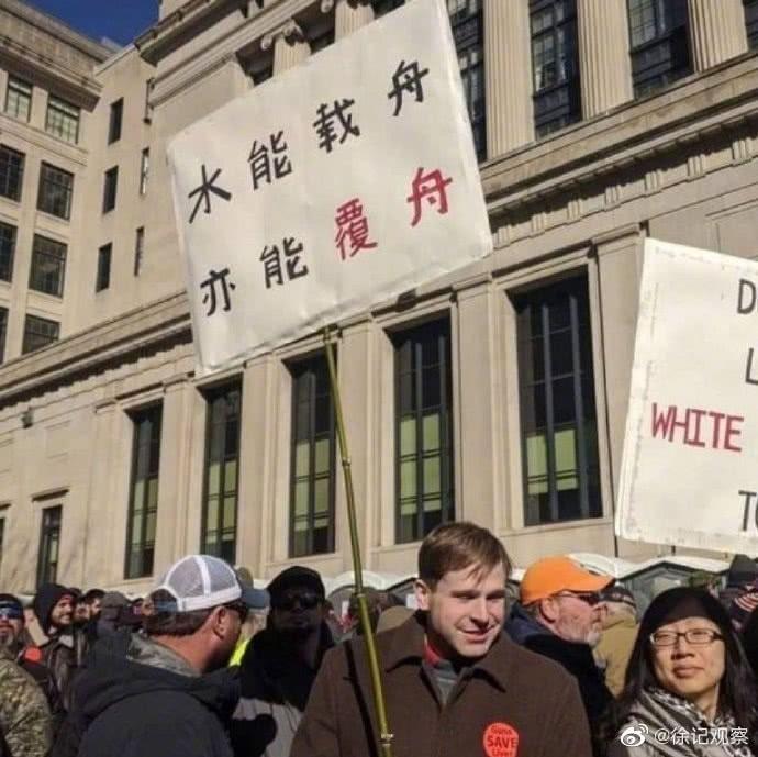 1名白人手持中文抗議標語,但其實這是今年1月的抗議事件,與目前的暴動無關。(圖取自微博)