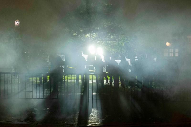 警方鎮暴部隊在鐵柵欄後方,手持盾牌築起人牆,並向群眾發射催淚瓦斯。(法新社)