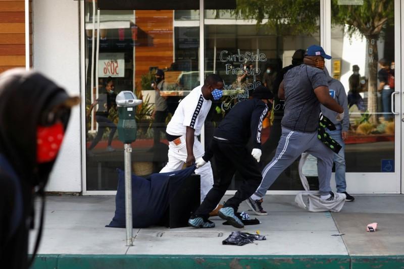 非裔男佛洛伊德(George Floyd)之死,在全美引發抗議行動,但卻出現許多搶劫放火的事件。圖為加州長灘多名男子拖著物品快跑。(路透)