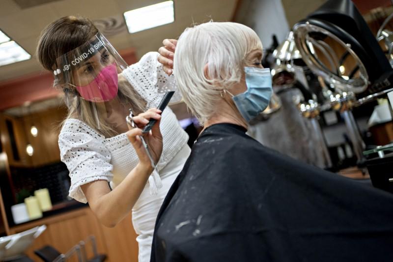 美國新病例持續增加,各行業開始要求員工及顧客簽下「冠狀病毒免責契約」,才能進行消費或工作。圖為美國德州一間髮廊。(彭博)