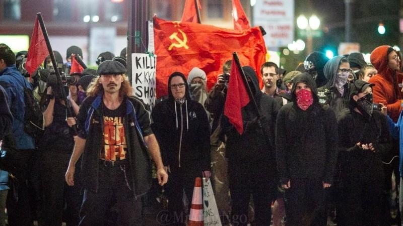 中國微博盛傳1張照片,內容顯示美國抗議人群中出現共產黨旗,聲稱明尼蘇達州的德盧斯市29日宣布起義發動共產革命,卻被中國網友打臉,是2018年10月奧勒岡州一場抗議的照片。(圖取自微博)